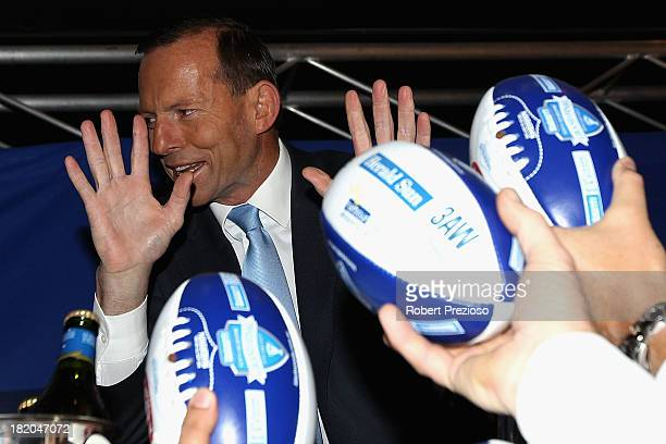 Prime Minister Tony Abbott signs footballs for fans during the 2013 Blackwoods North Melbourne Grand Final Breakfast at Etihad Stadium on September...