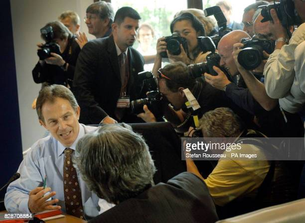 Prime Minister Tony Blair talks with his Japanese counterpart Junichiro Koizumi during a 'round the table' photocall with fellow world leaders of the...