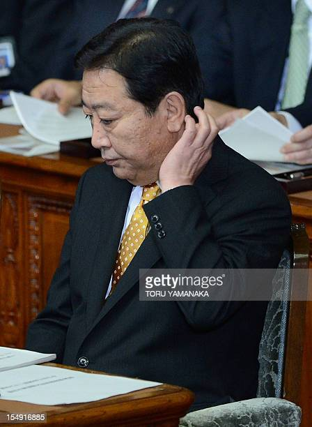 Prime Minister Yoshihiko Noda scratches the nape of his neck before delivering his policy speech at the lower house during the Extraordinary Diet...