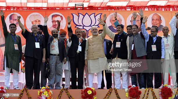 BJP prime ministerial candidate Narendra Modi waves along with Bhartiya Janta Party Senior state leaders during a public rally at Heera Nagar on...
