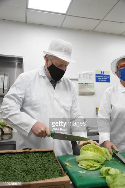 Prime Minster Boris Johnson cuts up a cabbage in the kitchens during a visit to the Royal Berkshire Hospital in Reading as part of a review of...