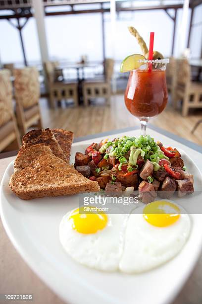 prime rib hash with two eggs and toast. - bloody mary stock photos and pictures