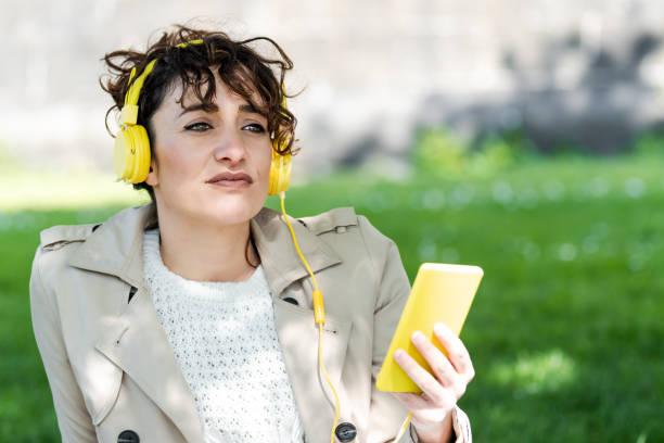Primer plano de una mujer muy atractiva que esta mirando a lo lejos mientras esta sentada en la hierba con su movil de carcasa amarilla en la mano. La mujer esta con unos auriculares con cable amarillos sobre la cabeza.