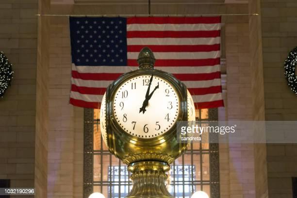 primer plano del reloj de grand central, en nueva york. al fondo la bandera americana, y a los lados parte de la decoración navideña - parte de stock pictures, royalty-free photos & images