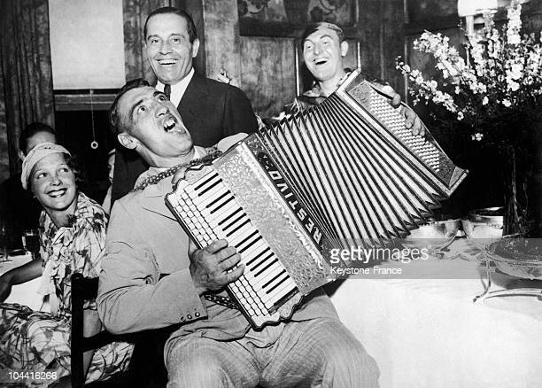 Primo CARNERA celebrating his victory in the world boxing championship all categories playing the accordeon and singing happily among smiling faces