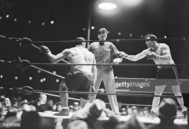 Primo Carnera slowly rises at the count of six as the referee holds off Jack Sharkey during their heavyweight bout at Ebbets Field. Sharkey defeated...
