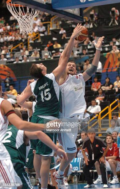 Primoz Brezec gets his hand on the ball as Turkey's Kurtoglu tries to score during the 2006 FIBA World Championships Eighth Final between Slovenia...