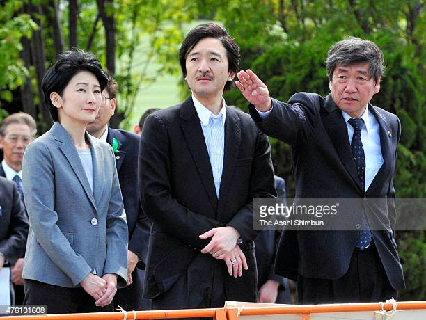Prince Akishino and Princess Kiko of Akishino listen to the explanation by a fishery industory staff during their visit to tsunamidevastated area to...