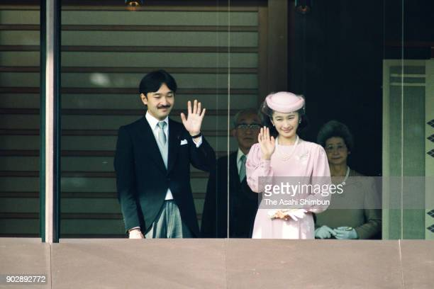 Prince Akishino and Princess Kiko of Akishino wave to wellwishers from a balcony to celebrate the emperor's 59th birthday at the Imperial Palace on...
