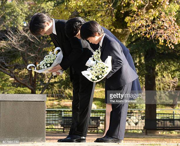 Prince Akishino Princess Kiko and their son Prince Hisahito bow prior to offering flowers at the Abomb Hypocenter Memorial at Nagasaki Hypocenter...
