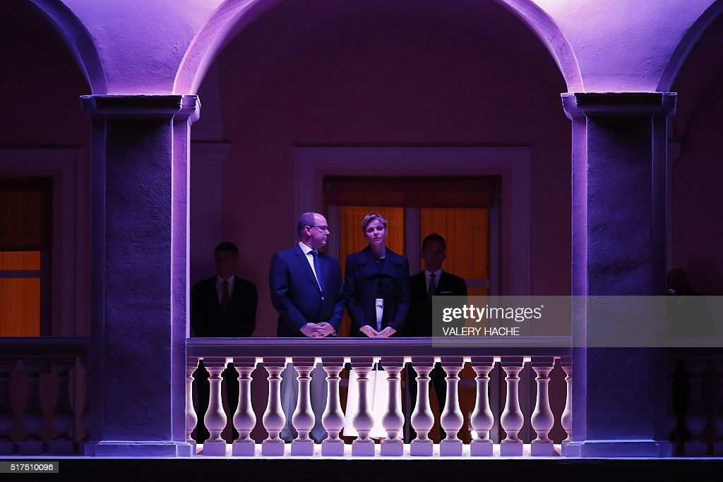 Prince Albert II de Monaco (L) and Princess Charlene of Monaco appear on the balcony of the prince's palace to celebrate Good Friday on March 25, 2016 in Monaco HACHE