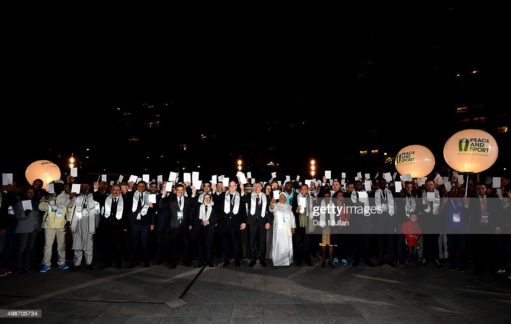 Prince Albert II of Monaco (c) and delegates hold white peace cards after completing a Peace Walk from the Fairmont Hotel to the Grimaldi Forum ahead of the Peace & Sport International Forum on November 25, 2015 in Monaco, Monaco.