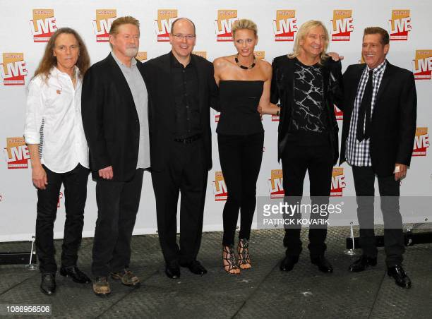 Prince Albert II of Monaco and his fiancee South African Charlene Wittstock pose with musicians of US band The Eagles before a concert at the Louis...
