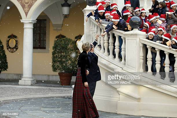 Prince Albert II of Monaco and his wife Charlene salute children as they arrive to take part in a Children's Christmas ceremony on December 18 2013...