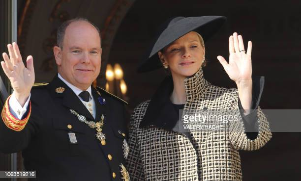 Prince Albert II of Monaco and his wife Princess Charlene of Monaco wave to the crowd as they appear on the balcony of the Monaco Palace during...