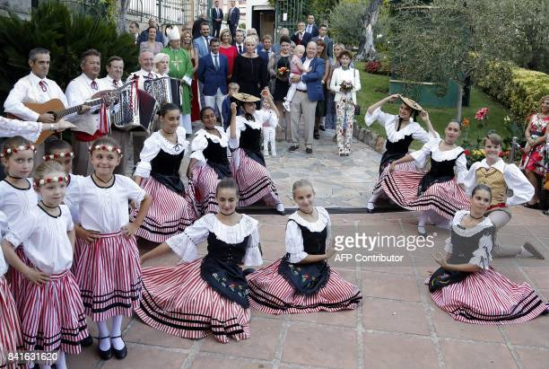 Prince Albert II of Monaco and his wife Princess Charlene their twins Prince Jacques Princess Gabriella and an unidentified child look at dancers...