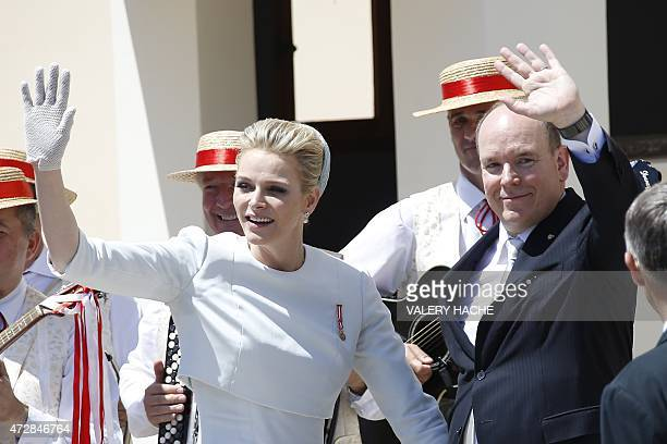 Prince Albert II of Monaco and his wife Princess Charlene wave as they greet the crowd outside the cathedral after the baptism of their twins Prince...
