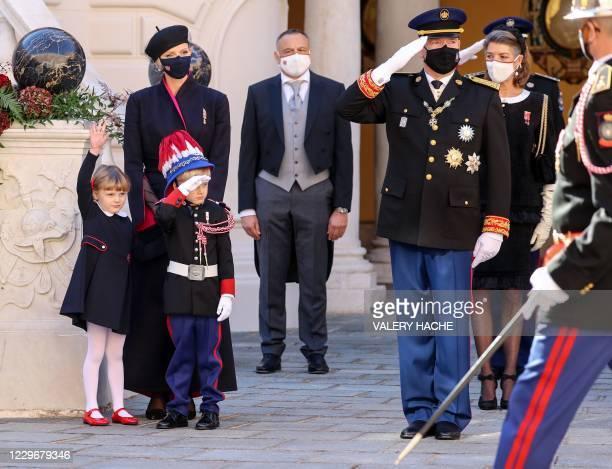 Prince Albert II of Monaco and Prince Jacques of Monaco salute next to Princess Charlene of Monaco and Princess Gabriella of Monaco during the...