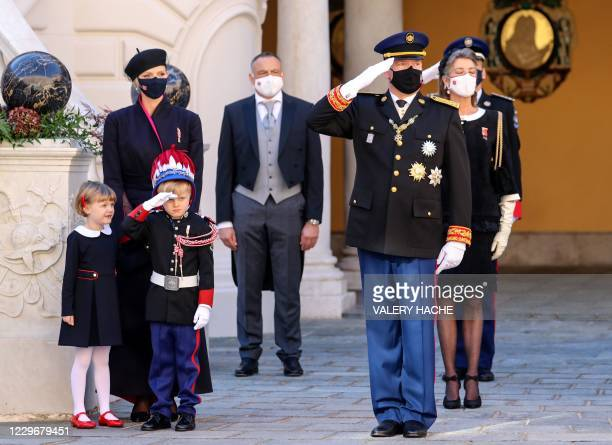 Prince Albert II of Monaco and Prince Jacques of Monaco salute next to Princess Charlene of Monaco and Princess Gabriella of Monaco during the...