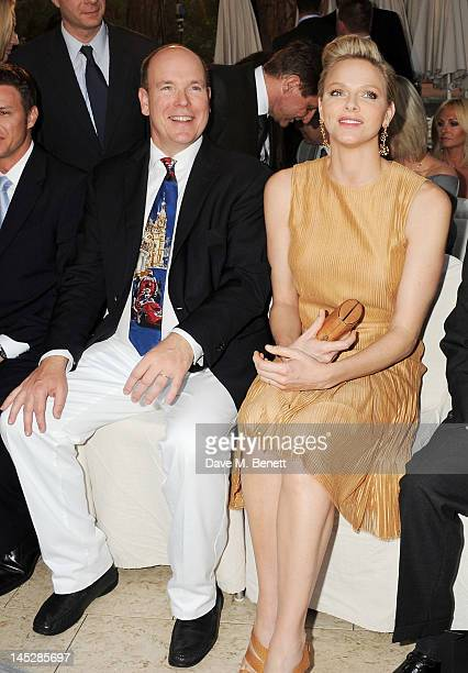 Prince Albert II of Monaco and Princess Charlene of Monaco attend a cocktail reception during Amber Lounge Fashion Monaco 2012 at Le Meridien Beach...