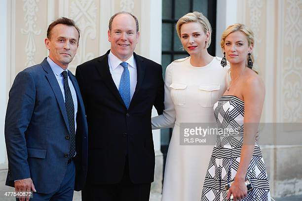 Prince Albert II of Monaco and Princess Charlene of Monaco pose with actor Robert Knepper and wife during the Monaco Palace cocktail party of the...