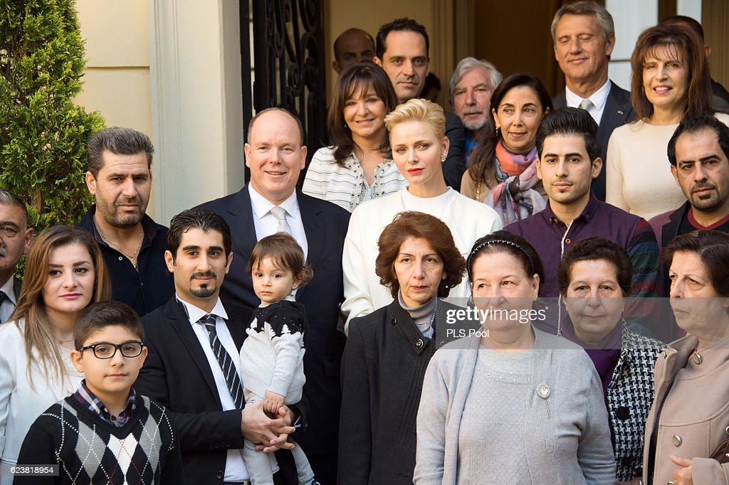 Prince Albert II of Monaco and Princess Charlene of Monaco pose with refugees during the Parcels Distribution At Monaco Red Cross Headquarters on November 17, 2016 in Monaco, Monaco.