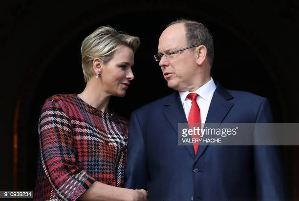 Prince Albert II of Monaco and Princess Charlene of Monaco speak with each other as they appear on the palace's balcony during Sainte Devote...