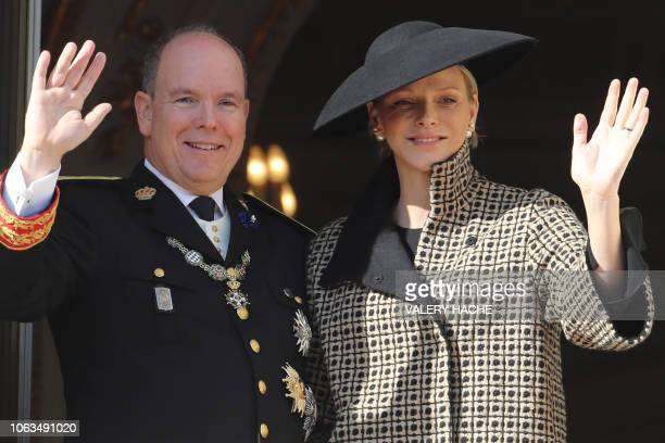 Prince Albert II of Monaco and Princess Charlene of Monaco wave as they appear on the balcony of the Monaco Palace during the celebrations marking...