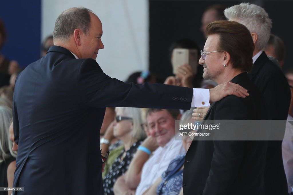 Prince Albert II of Monaco (L) greets Irish singer Bono (R) as they attend a commemorative ceremony marking the first anniversary of a jihadist truck attack which killed 86 people in Nice, southern France, on Bastille Day, July 14, 2017. Bastille Day celebrations were tinged with mourning, as the Mediterranean city of Nice payed tribute to the victims of an attack claimed by the Islamic State group one year ago, where a man drove a truck into a crowd, killing 86 people. / AFP PHOTO / Valery HACHE