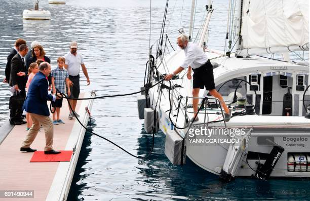 Prince Albert II of Monaco helps to moor the OceanoScientific Explorer sailing boat called Boogaloo steered by French sailor Yvan Griboval at the...