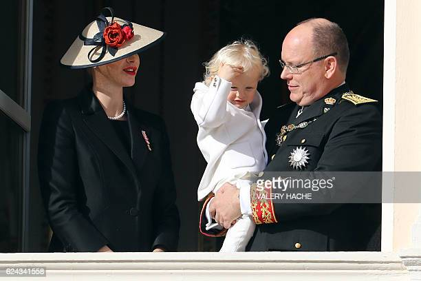 Prince Albert II of Monaco holding Prince Jacques and princess Charlene of Monaco appear on the balcony of the Monaco Palace during the celebrations...