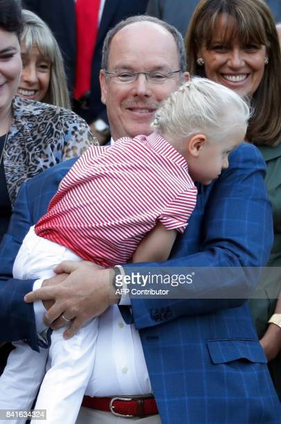 Prince Albert II of Monaco holds his son Prince Jacques as they take part in the traditional Monaco's picnic in Monaco on September 1 2017 / AFP...