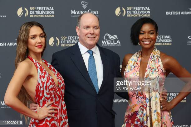 Prince Albert II of Monaco poses with US actress Jessica Alba and US actress Gabrielle Union during a photocall as they arrive for the opening...