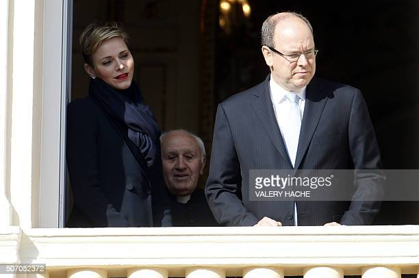 Prince Albert II of Monaco Princess Charlene and Monaco Palace chapel priest Cesar Penzo appear on the balcony of the prince's palace during the...