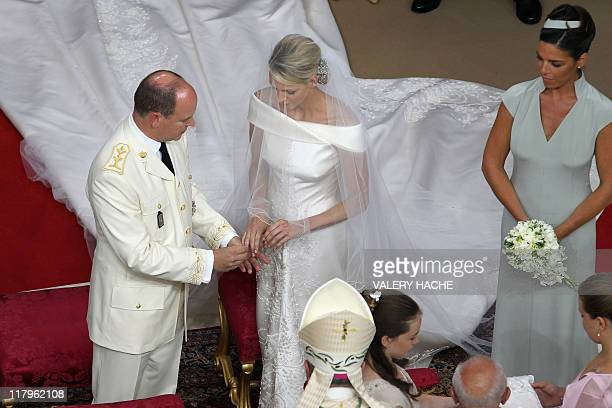Prince Albert II of Monaco puts the ring on Princess Charlene of Monaco finger next to maid of honour Donatella Knecht de Massy during their...