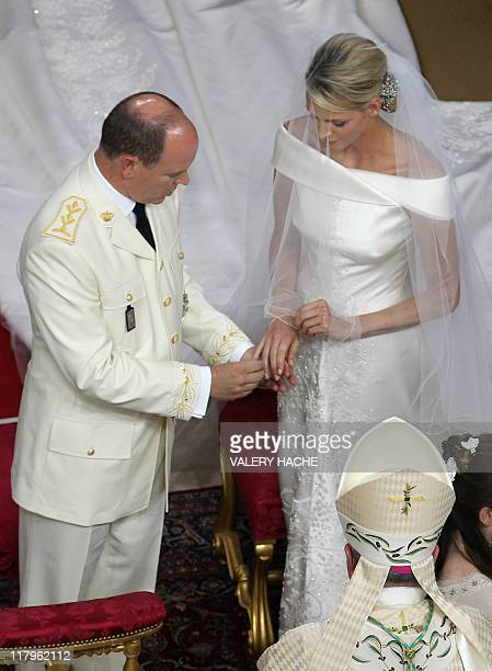 Prince Albert II of Monaco puts the ring on Princess Charlene of Monaco finger during their religious wedding at the Main Courtyard of the Prince's...