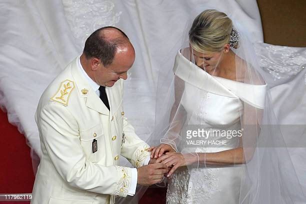 Prince Albert II of Monaco puts the ring on the finger of the left hand of Princess Charlene of Monaco at the altar during their religious wedding at...