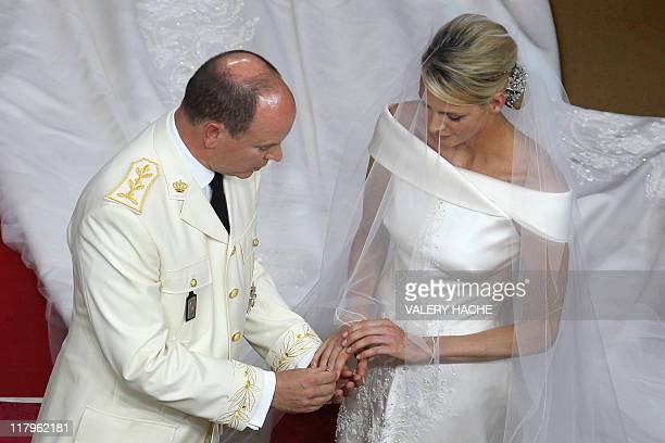 Prince Albert II of Monaco puts the ring on the finger of the right hand of Princess Charlene of Monaco at the altar during their religious wedding...