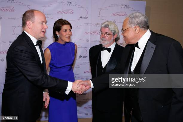 Prince Albert II of Monaco shakes hands with James Earl Jones beside Princess Caroline of Hanover and director George Lucas during the 25th...