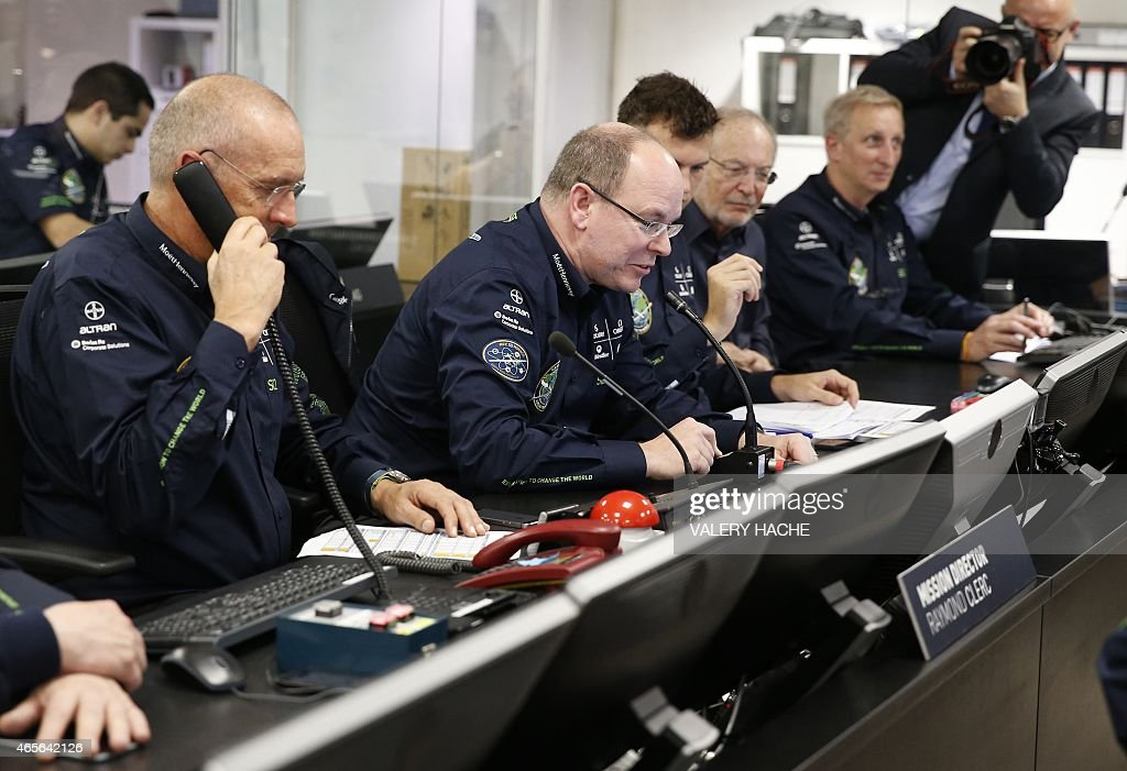 Prince Albert II of Monaco (C) speaks into a communications console at the control centre for the Solar Impulse 2 solar powered aircraft in Monaco early on March 9, 2015, during the planes take-off from Abu Dhabi in the first attempt to fly around the world in a plane using solar energy. The flight of Solar Impulse 2 will cap 13 years of research and testing by two Swiss pilots with a round-the-world trip in which it will land 12 times and last about 25 days spread over five months.