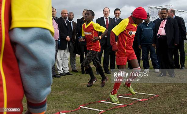 Prince Albert II of Monaco watches young football enthusiasts train on 12 June 2010 while visiting the Ikhaya Lemidlalo Project at the Gugulethu...