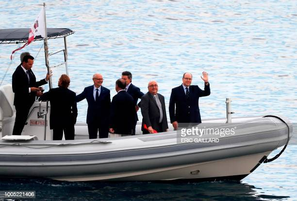 Prince Albert II of Monaco waves from a boat with dignitaries including Archbishop of Monaco Bernard Barsi during a presentation on the...