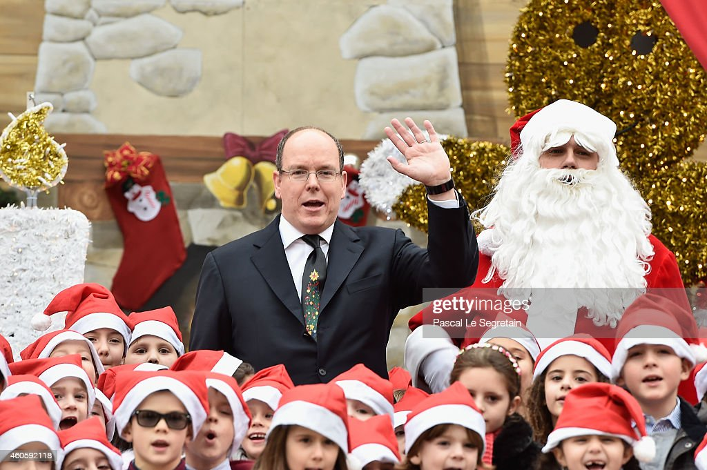 Prince Albert II of Monaco waves next to Santa Claus in the courtyard of the Monaco Palace during the Christmas gifts distribution on December 17, 2014 in Monaco, Monaco.