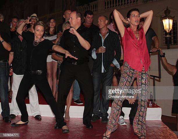 Prince Albert II of Monaco with his fiancee Charlene Wittstock, left, and his sister Princess Caroline of Hanover dance during the open-air concert...