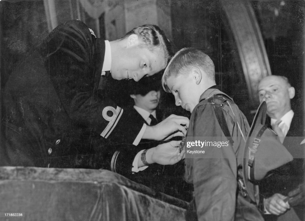 Prince Albert of Belgium, later King Albert II of Belgium awards 10 year old Jean-Claude Genot a prize for bravery at the Academy Palace after he saved the life of a drowning girl who had fallen in a River, Brussels, circa 1960.