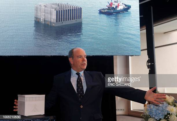 Prince Albert of Monaco poses with a model the principality's offshore land reclaimation extension project concretefilled chambers called caissons...