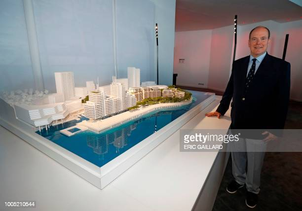 Prince Albert of Monaco poses with a model the principality's offshore land reclaimation extension project which is set to reclaim some 15 acres from...