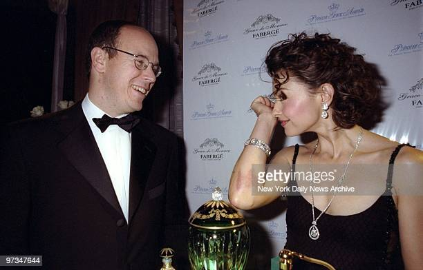 Prince Albert of Monaco watches as Ashley Judd samples the scent at the WaldorfAstoria where they unveiled the Grace de Monaco Parfum Collection by...