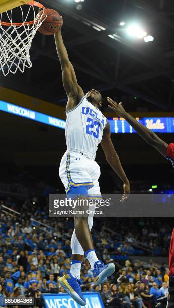 Prince Ali of the UCLA Bruins gets past Isaiah Jones of the Detroit Mercy Titans for a dunk in the second half of the game at Pauley Pavilion on...