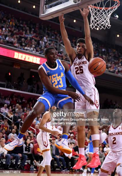 Prince Ali of the UCLA Bruins passes past Bennie Boatwright of the USC Trojans in the first half of a NCAA basketball game at the Galen Center on...